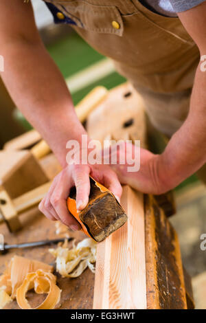 Carpenter working with a sanding block and sandpaper in his workshop - Stock Photo