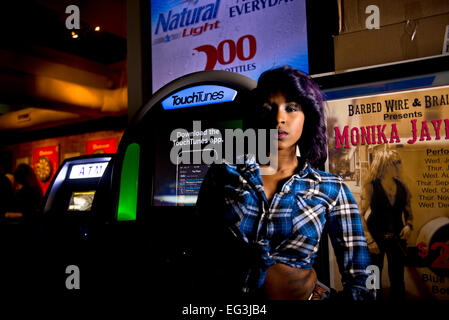 African American Model standing by a jukebox in a bar - Stock Photo
