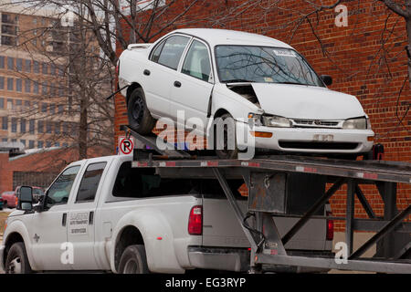 Damaged car loaded on auto transport trailer - Virginia USA - Stock Photo