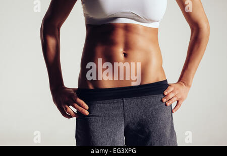 Mid section of fit woman's torso with her hands on hips. Female in sportswear with perfect muscular abs on grey - Stock Photo