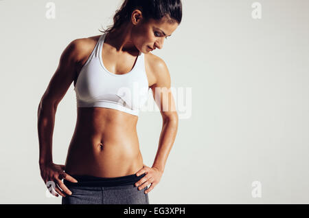 Attractive young woman in sportswear posing on grey background. Slim and healthy female model in studio. - Stock Photo