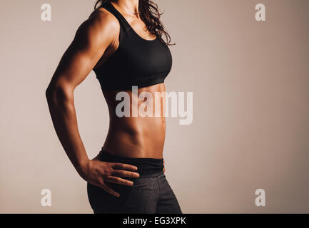 Cropped shot of fit woman's torso with her hands on hips. Female with perfect abdomen muscles. - Stock Photo