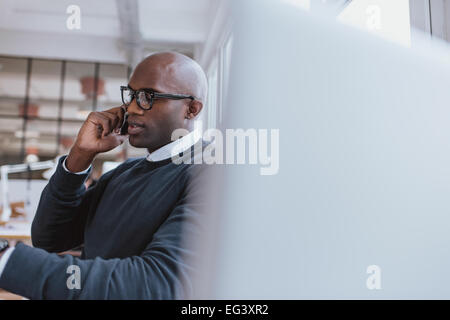 Shot of a young businessman talking on cellphone while at work. Bald african executive in conversation with client - Stock Photo