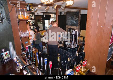 Bar & barman inside The Fox pub / public house / tavern. Church St. Twickenham UK; popular with Rugby fans on match - Stock Photo