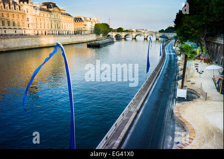 River Seine and Paris Plage - a summer beach beside the river. Barge moving on the river near bridge. Paris, France. - Stock Photo