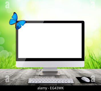 Modern computer display with spring meadow and butterfly, placed on wooden planks. Concept of spring shopping and - Stock Photo