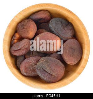 Sun dried apricots in wooden bowl isolated on white background. - Stock Photo