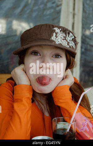 Naughty girl with cap sticking out her tongue, Corsica, France - Stock Photo