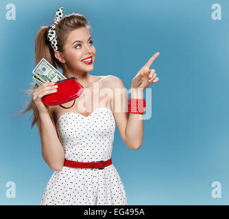 Attractive young lady holding cash and shows forefinger. Shopping concept - Stock Photo