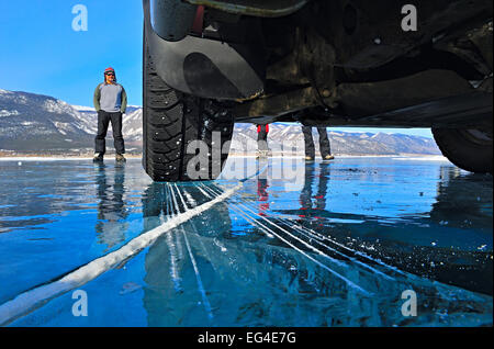 View people standing on ice underneath car on the ice Lake Baikal Siberia Russia March. Property released Model - Stock Photo