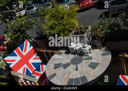Pot plants, deck chairs and garden table on a balcony in Primrose Hill, London, England - Stock Photo