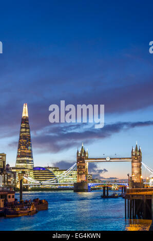 Tower Bridge and The Shard viewed from the north bank of the Thames at night. London, UK - Stock Photo