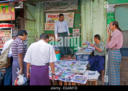 Burmese men buying daily newspapers and journals at street stall in Yangon / Rangoon, former capital city of  Myanmar - Stock Photo