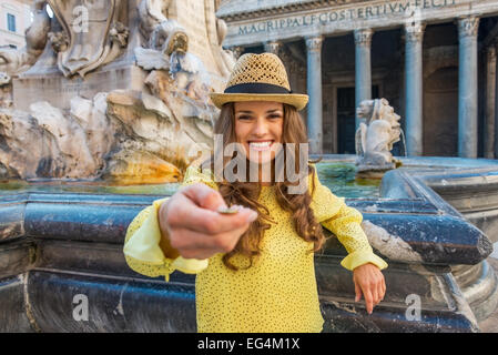Young woman tossing coin near fountain of the pantheon in rome, italy - Stock Photo