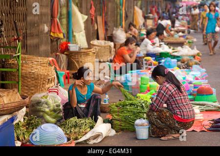 Burmese female street vendors selling food and goods on the ground at market in Yangon / Rangoon, Myanmar / Burma - Stock Photo