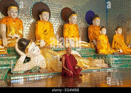 Buddhist monk praying in front of Buddha statues in the Shwedagon Zedi Daw Pagoda at Yangon / Rangoon, Myanmar / - Stock Photo