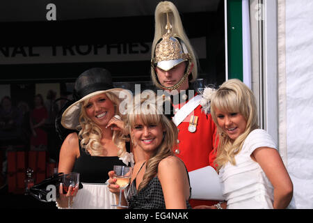 Three ladies pose with one of the uniforms guarding the Grand National Meeting trophies / Ladies Day / Aintree Racecourse - Stock Photo