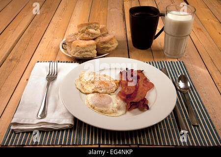 A breakfast of bacon, eggs, and biscuits. - Stock Photo