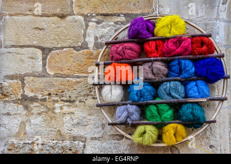 Balls of brightly coloured wool in a circular display on a brick wall - Stock Photo