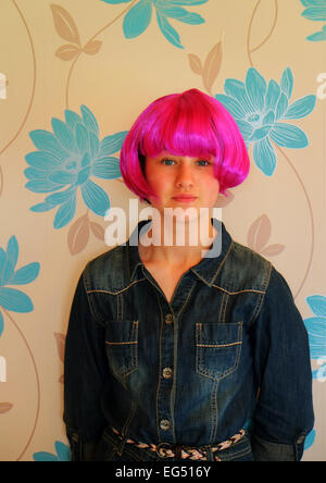 Young Irish girl wearing a vivid pink party wig full face head on. - Stock Photo