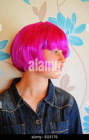 Young Irish girl wearing a vivid pink party wig , shown in profile - Stock Photo