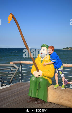 Wooden fishermen statue on the new pier in  Niendorf, Baltic Sea coast, Schleswig-Holstein, Germany, Europe - Stock Photo