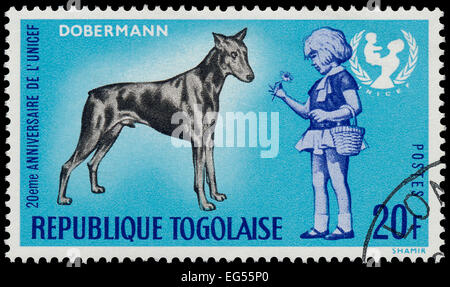 TOGO - CIRCA 1967: A stamp printed by Togo, shows The 20th Anniversary of UNICEF and dobermann dog, circa 1967 - Stock Photo