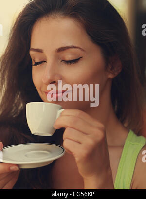 Beautiful happy woman drinking coffee with closed eye. Closeup vintage portrait - Stock Photo
