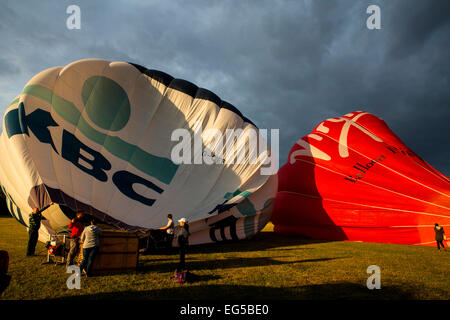 Teamwork preparation for tethered hot air balloons against dramatic sky, South Oxfordshire, EnglandHot air balloon - Stock Photo