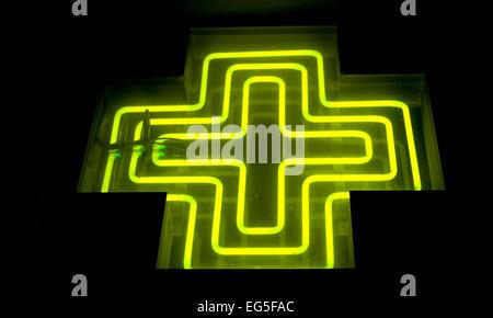 Pharmacy neon green cross sign at night - Stock Photo