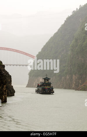 Misty gorge with a Chinese river cruise boat and the New Dragon Gate Bridge, Wushan, China - Stock Photo