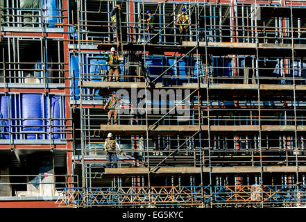 Builders working on scaffolding on a new steel framed building. - Stock Photo