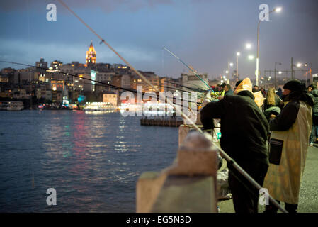 Fishermen line the edge of Galata Bridge with their lines over the side into the Golden Horn. Spanning the Golden - Stock Photo