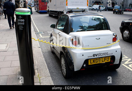An Electric powered mini car parked in a battery charging bay in central London, England - Stock Photo