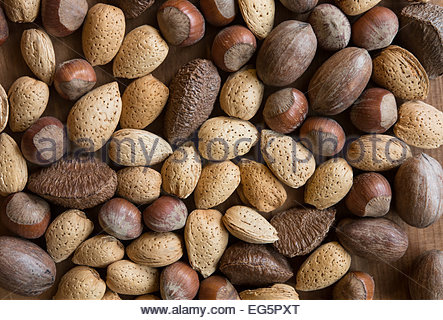 Mixed nuts in shells on wooden surface - Stock Photo