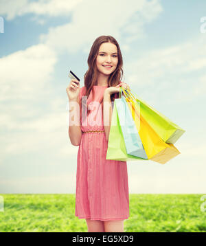 smiling woman in dress with many shopping bags - Stock Photo