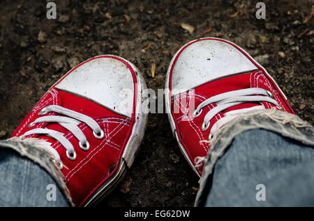 Feet in dirty red sneakers and jeans outdoors. Making first step. - Stock Photo