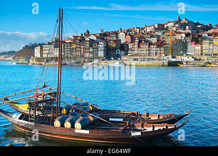 Traditional boat with wine barrels. Porto Old Town on the background. Portugal - Stock Photo