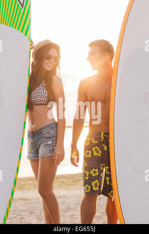 smiling couple in sunglasses with surfs on beach - Stock Photo