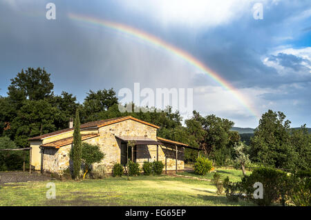 Rural cottage in Tuscany, italy, after a rainstorm, rainbow in the sky - Stock Photo