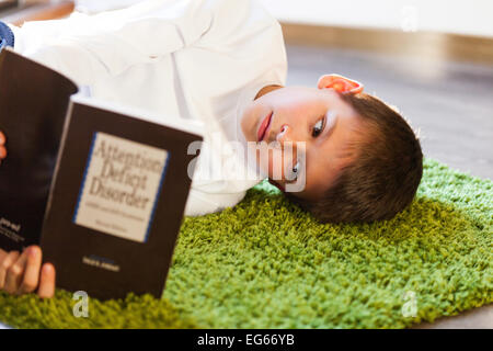 boy reading a book on ADD - Stock Photo