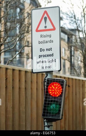 Warning sign and light at a set of rising bollards, to prevent vehicular access. - Stock Photo