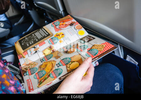 A woman reads the in-flight menu on a plane - Stock Photo