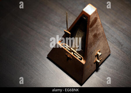 Vertical shot of a vintage metronome, on a dark background. - Stock Photo