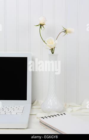 Closeup of a white wood desk with a white laptop and milky vase with white roses. A spiral bound pad an some flower - Stock Photo