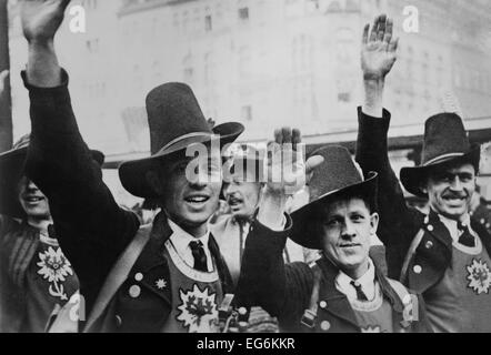 Men in Tyrolean costume celebrate the German annexation of Austria with a Nazi salute. Nazi ideology integrated - Stock Photo