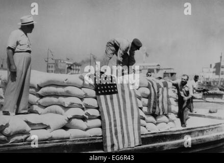 Sacks of flour, the first relief supplies from the United States, being unloaded in the port of Piraeus. American - Stock Photo