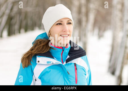 Cheerful young sport woman at winter outdoor activity. Smiling caucasian girl jogging in winter park - Stock Photo