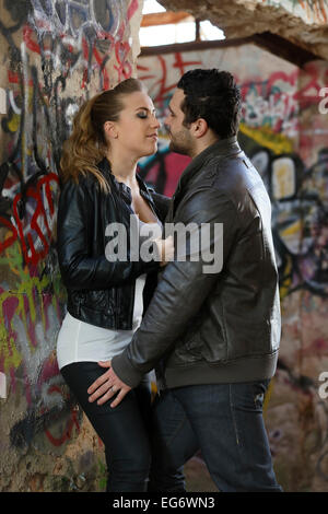 Young couple kissing in a ruined building covered in graffiti - Stock Photo