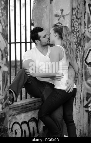 Young couple kissing at a barred window in a ruined building covered in graffiti - Stock Photo